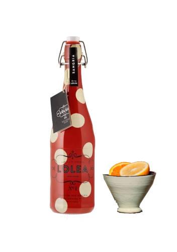 Botella de sangria tinta lolea y vaso con gajos de naranja